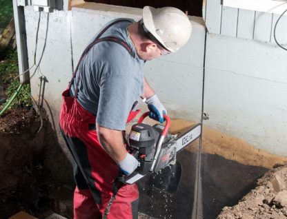 Contractor with the 680ES Gas Chainsaw in action on a job site, making a clean, deep cut in a concrete wall.